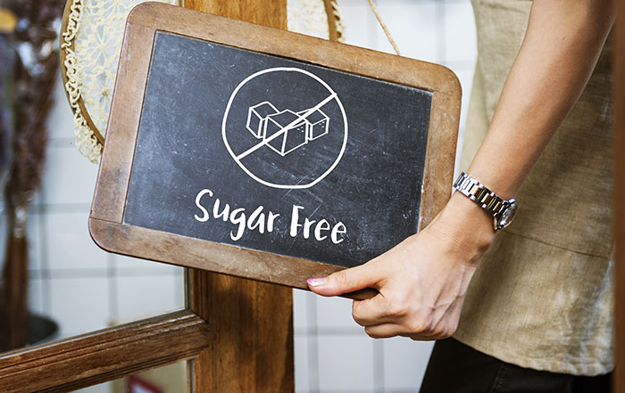Lady with black board sign sugar free